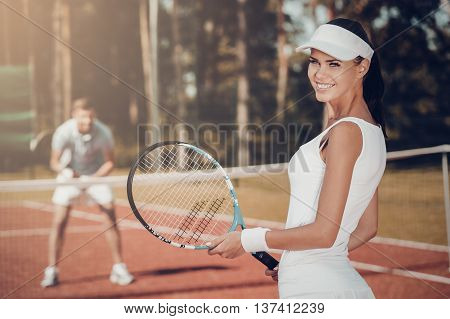 Enjoying the game. Beautiful young woman holding tennis racket and looking over shoulder with smile while man in sports clothing standing in the background