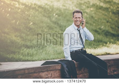 Sharing great news. Confident mature businessman talking on the mobile phone and smiling while sitting at the quayside