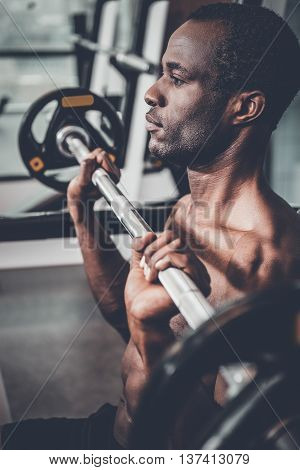 Training on bench press. Side view of confident young African man working out on bench press