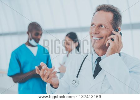 Good news! Cheerful mature doctor talking on the mobile phone and gesturing while his colleagues talking in the background