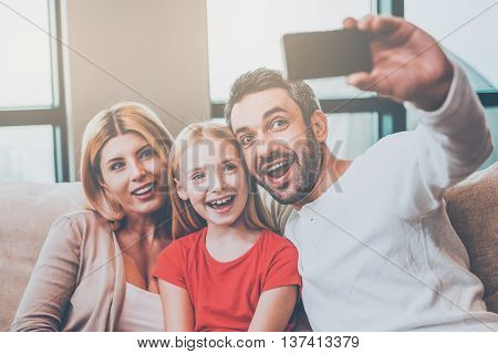 Family selfie. Happy family of three bonding to each other and smiling while father photographing them with smart phone