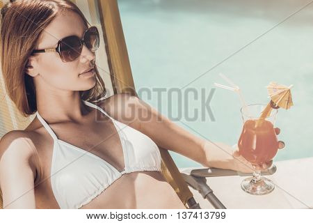Enjoying vacation. Beautiful young woman in white bikini holding glass with cocktail while relaxing in deck chair near the pool