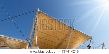 Detail of a modern tensile structure membrane fabric roof with poles and steel cables on a blue clear sky with sun rays
