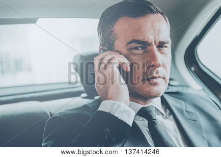 Businessman on the phone. Confident mature businessman talking on the mobile phone and looking away while sitting on the back seat of a car