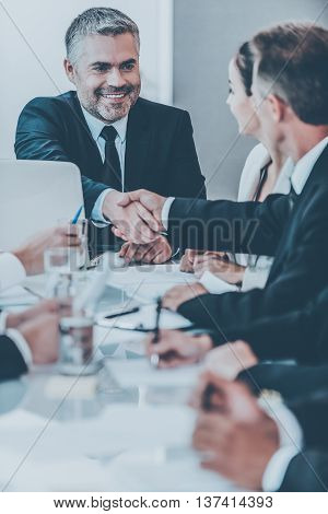 My congratulations! Confident mature man in formalwear shaking hand to one of his colleagues and smiling while sitting at the table together