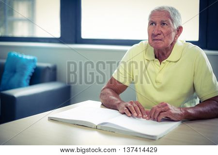 Senior blind man reading a braille book at home