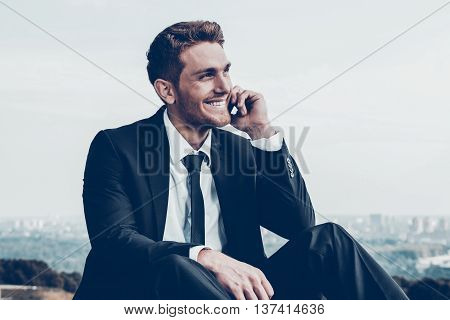 Business talk. Confident young man in formalwear talking on the mobile phone and smiling while sitting outdoors with cityscape in the background