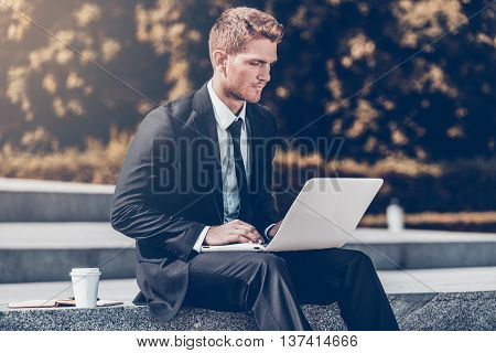 Having opportunity to work anywhere. Confident young man in shirt and tie working on laptop while sitting outdoors