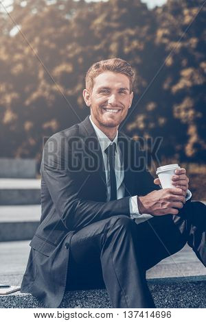 Enjoying coffee break on fresh air. Handsome young man in formalwear drinking coffee and smiling while sitting outdoors