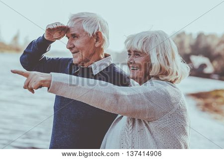 Just look at that! Happy senior couple standing on the quayside together while woman pointing away and smiling