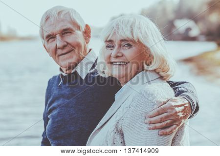 Happy to be together. Happy senior couple bonding to each other and smiling while standing on the quayside together