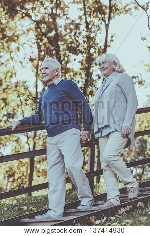 Happy to be together. Full length of happy senior couple holding hands and moving down by wooden staircase