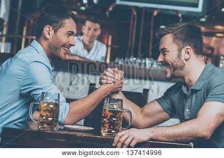 Old friends meeting. Two cheerful young men drinking beer and having fun in bar