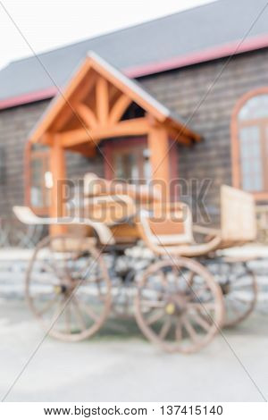 Blurred photo of wagon retro style parks in front of farmland house background.