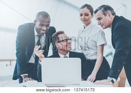 Discussing some business issues. Business people in formalwear discussing something while man pointing a paper with a pen and smiling