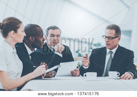 Discussing business together. Business people in formalwear discussing something while sitting together at the table