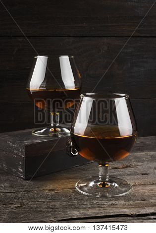 Cognac In Two Glasses On A Dark Wooden Background