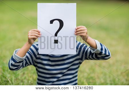 Boy in park covering his face with a placard that shows question mark sign