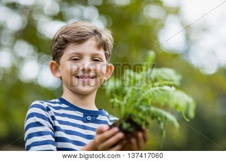 Portrait of smiling boy holding sapling plant in park