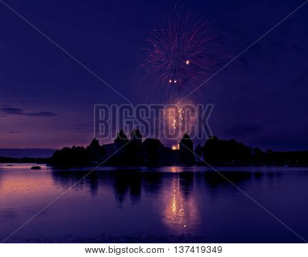 Fireworks in Trakai, Lithuania. Amazing sunset and fireworks with reflection on a water in Lithuania, Trakai