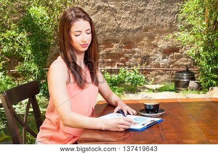 Business Woman Writing On Clipboard Outside On Terrace