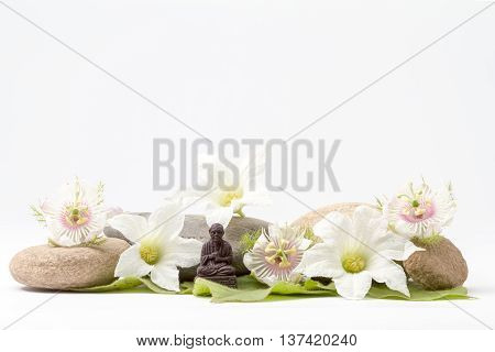 several boulders and granadilla flower in close up and and wisdom Buddha