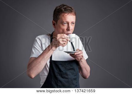 A middle age man drink and taste a cup of coffee