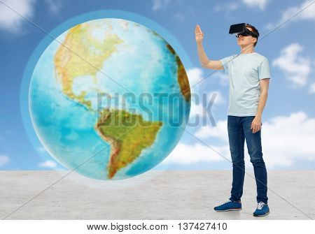 3d technology, virtual reality, entertainment, cyberspace and people concept - happy man with virtual reality headset or 3d glasses playing game and touching earth globe over sky and clouds background