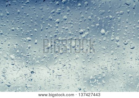 Background of rain drops on a window glass, toned blue