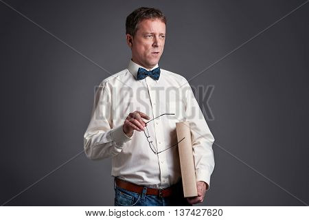 A middle age man standing and talking to someone wearing a bowtie