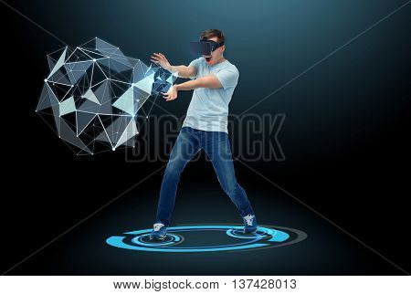 3d technology, virtual reality, entertainment and people concept - happy young man in virtual reality headset or 3d glasses playing with low poly shape projection over black background
