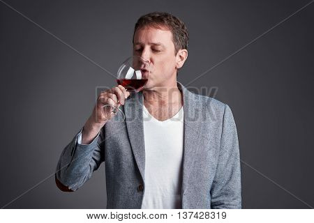 A middle age man drinking and tasting a glass red wine