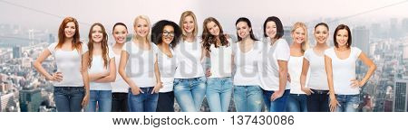friendship, diversity, body positive and people concept - group of happy different size age and ethnicity women in white t-shirts hugging over city skyscrapers background