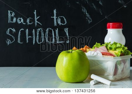 Lunch box with sandwich and fruits infront of chalk board, copy space