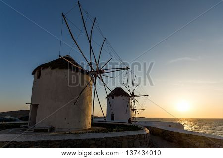 Sunset of White windmills and Aegean sea on the island of Mykonos, Cyclades, Greece