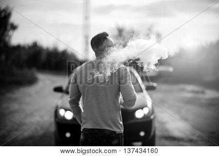 Vaper With Beard In Sunglasses Vaping Outdoor, Focus On Steam