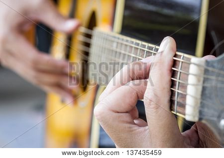 Hand playing acoustic guitar close up. music