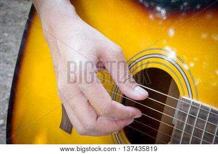 Hand playing acoustic guitar close up. musuc.