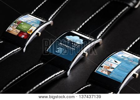 modern technology, object and media concept - close up of black smart watch set with weather cast and business news application