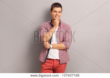 Confident casual man standing against a gray wall and posing