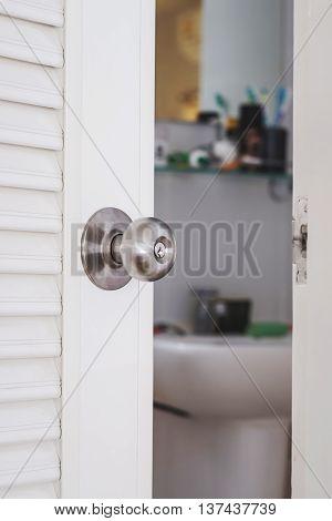Close-up stainless door knob, with door open slightly
