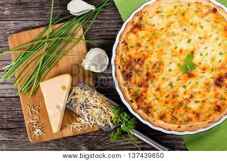 French onion cheese quiche or pie in a gratin dish sprinkled with parsley with grater and ingredients on cutting board authentic recipe view from above