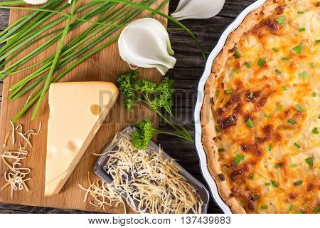 French onion cheese quiche or pie in a gratin dish sprinkled with parsley with grater and ingredients on cutting board authentic recipe view from above close-up