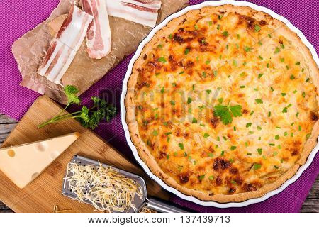 French onion quiche or pie in a gratin dish on table mat with grater piece of cheese on cutting board and slices of bacon on parchment paper view from above close-up