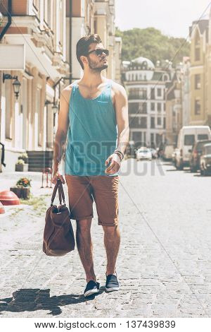 Exploring city. Full length of handsome young man in casual wear carrying bag and looking away while walking along the street