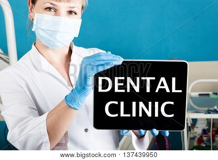 technology, internet and networking in medicine concept - femail dentist holding a tablet pc with dental clinic sign. at the dental equipment background.
