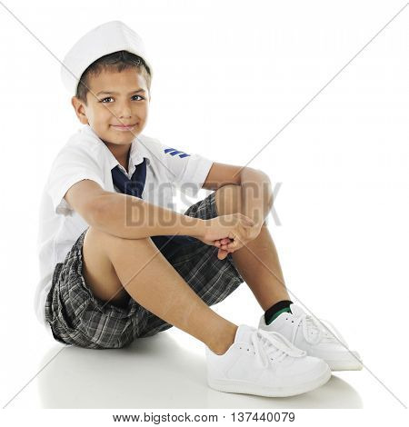 Full-length image of a smiling elementary boy sitting in his sailor shirt, tie and hat.  On a white background.