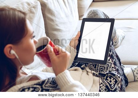 Woman in home cozy clothes sitting on a sofa using tablet with headphones, holding a red cup of coffee hands. Online education concept. e-learning. back view
