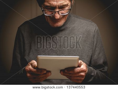 Senior with glasses with a tablet in hands. Online education retirement concept. e-Learning. mock up. Photo in low key