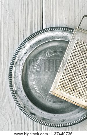 Metal plate with grater on the white wooden table